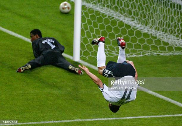 Germany's forward Miroslav Klose makes a flip after scoring the second goal as Saudi Arabia's goalie Mohammed Al Deayea at looks on at the Sapporo...
