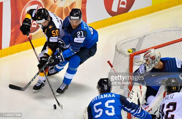 Germany's forward Patrick Hager and Finland's forward Juhani Tyrvainen vie for the puck as Finland's defender Atte Ohtamaa Finland's goalkeeper Kevin...