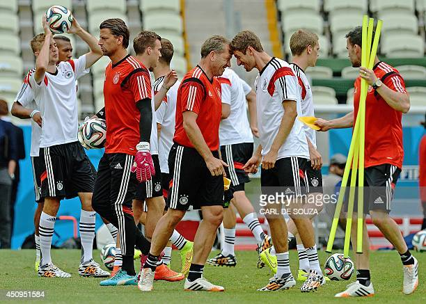 Germany's forward Thomas Mueller and goalkeeping coach Andreas Köpke joke during a training session at the Castelao stadium in Fortaleza on June 20...