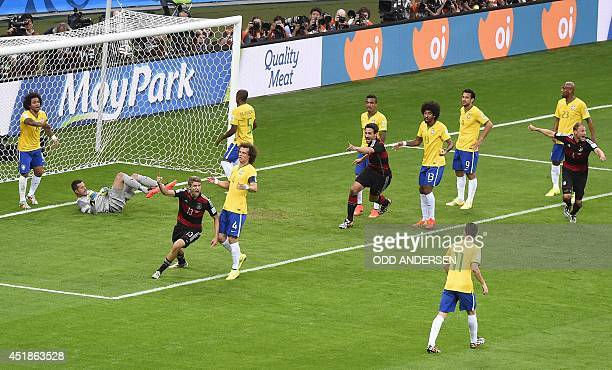 Germany's forward Thomas Mueller celebrates after scoring during the semifinal football match between Brazil and Germany at The Mineirao Stadium in...