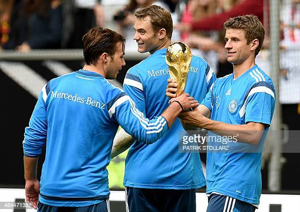 Germany's forward Thomas Mueller Germany's forward Mario Goetze and goolkeeper Manuel Neuer present the World Cup trophy to fans during a public...