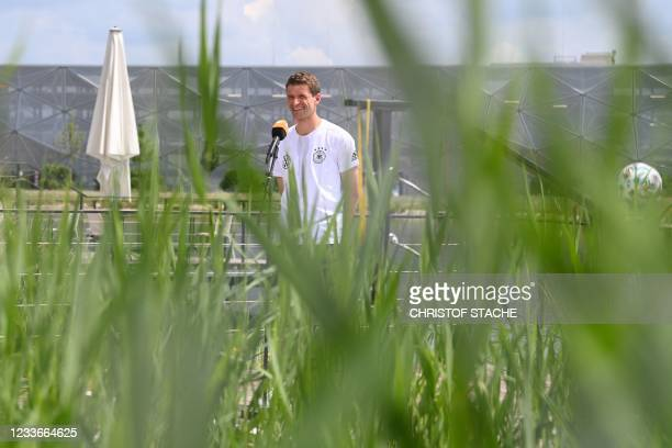 Germany's forward Thomas Mueller gives an interview after a training session at the team base camp in Herzogenaurach on June 26, 2021 during the EUFA...