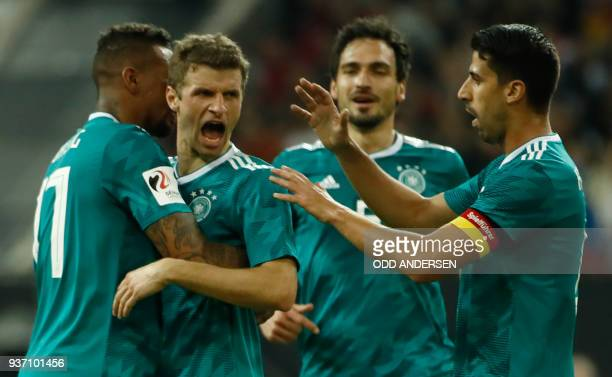 Germany's forward Thomas Mueller is congratulated by his teammates Germany's defender Jerome Boateng Germany's defender Mats Hummels and Germany's...