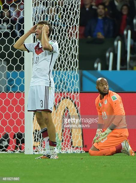 Germany's forward Thomas Mueller reacts after missing a shot on goal as Algeria's goalkeeper Rais Mbohli looks on during a Round of 16 football match...