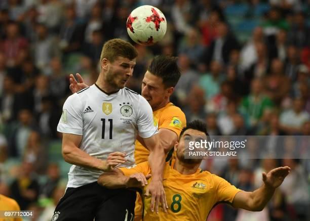 Germany's forward Timo Werner jumps for the ball against Australia's defender Milos Degenek and Australia's defender Bailey Wright during the 2017...