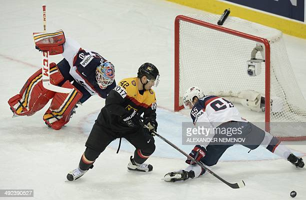 Germany's forward Yasin Ehliz vies with US defenceman Dan DeKeyser in front of US goalie Tim Thomas during a preliminary round group B game Germany...