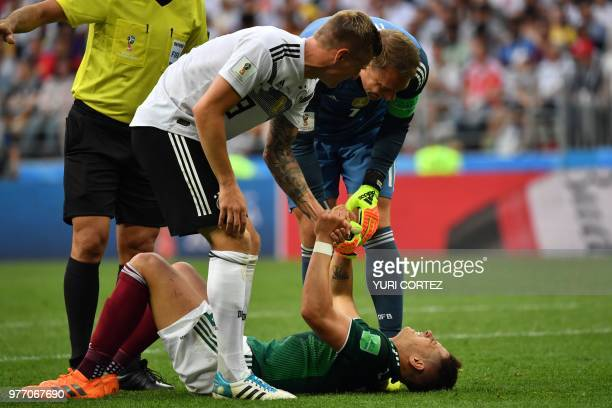 Germany's goalkeeper Manuel Neuer and Germany's midfielder Toni Kroos help Mexico's forward Javier Hernandez lying on the pitch during the Russia...
