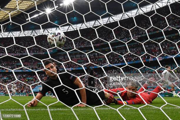 Germany's goalkeeper Manuel Neuer concedes England's first goal scored by forward Raheem Sterling during the UEFA EURO 2020 round of 16 football...