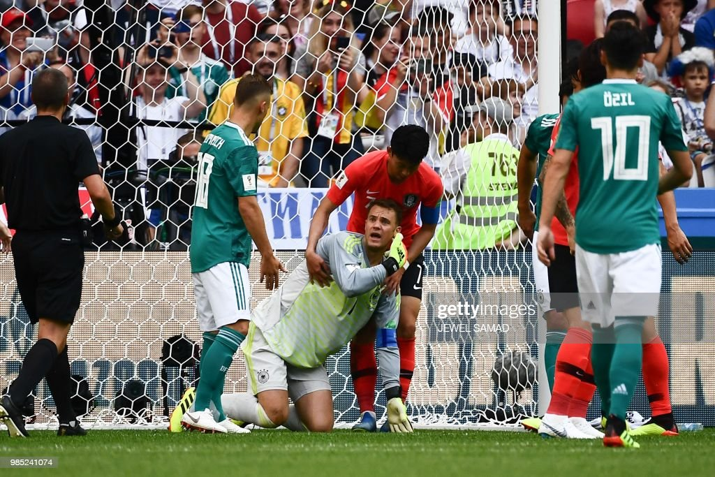 Germany's goalkeeper Manuel Neuer (C) reacts as South Korea's forward Son Heung-min (rear C) helps him to stand up during the Russia 2018 World Cup Group F football match between South Korea and Germany at the Kazan Arena in Kazan on June 27, 2018. (Photo by Jewel SAMAD / AFP) / RESTRICTED