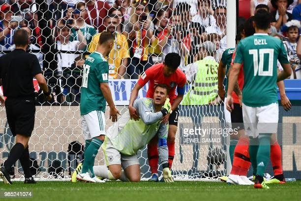 Germany's goalkeeper Manuel Neuer reacts as South Korea's forward Son Heungmin helps him to stand up during the Russia 2018 World Cup Group F...