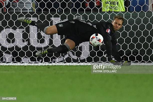 Germany's goalkeeper Manuel Neuer stops the ball during a penalty shootout of the Euro 2016 quarter-final football match between Germany and Italy at...
