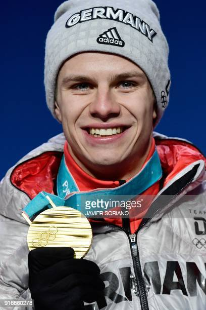 Germany's gold medallist Andreas Wellinger poses on the podium during the medal ceremony for the ski jumping Men's Normal Hill Individual at the...
