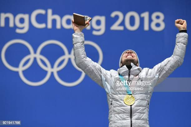 Germany's gold medallist Johannes Rydzek poses on the podium during the medal ceremony for the nordic combined Individual Gundersen LH/10km at the...