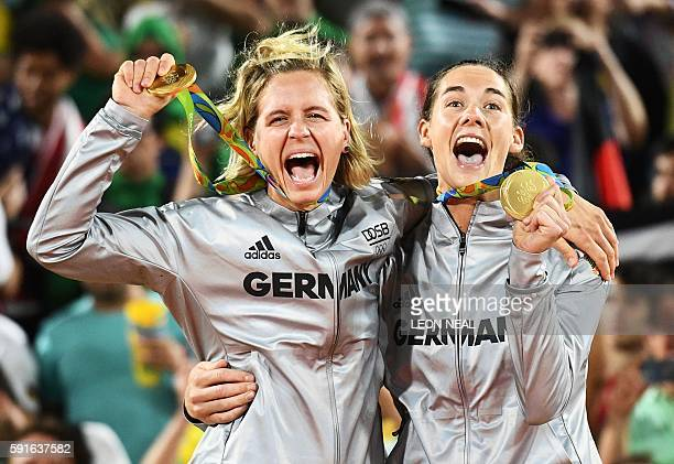 Germany's gold medallists, Laura Ludwig and Kira Walkenhorst, celebrate on the podium at the end of the women's beach volleyball event at the Beach...
