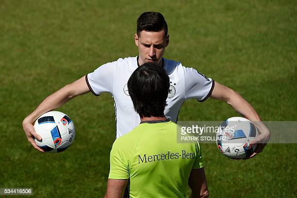 Germany's head coach Joachim Loew talks to Germany's midfielder Julian Draxler during a training session as part of the team's preparation for the...