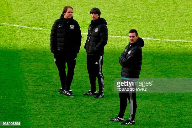 Germany's head coach Joachim Loew talks with Germany's assistant coach Thomas Schneider and coaching staff Miroslav Klose as they attend a training...