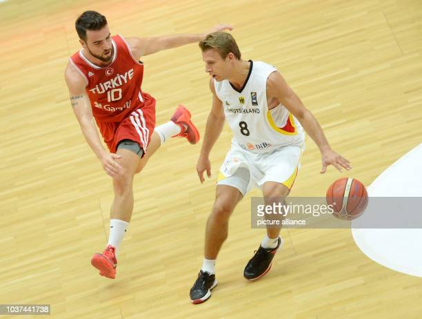 Germany's Heiko Schaffartzik and Turkey's Melih Mahmutoglu vie for the ball during the Supercup basketball match against Turkey in Hamburg Germany 23...