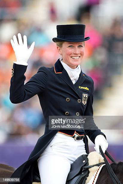 Germany's Helen Langehanenberg on Damon Hill waves to the crowd after competing in the team Dressage Grand Prix event of the 2012 London Olympics at...