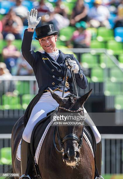 Germany's Isabell Werth on Weihegold Old waves after performing her routine to win the silver medal in the Equestrian's Dressage Grand Prix Freestyle...