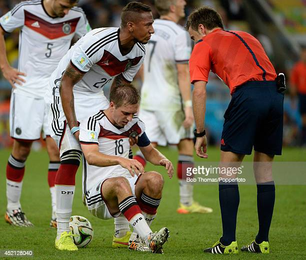 Germany's Jerome Boateng helps teammate Philipp Lahm to his feet during the 2014 FIFA World Cup Brazil Final match between Germany and Argentina at...