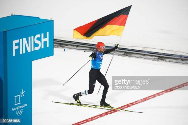 TOPSHOT Germany's Johannes Rydzek holding a German flag crosses the finish line in the nordic combined team Gundersen LH/4x5km cross country at the...