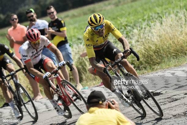 Germany's John Degenkolb and Belgium's Greg Van Avermaet , wearing the overall leader's yellow jersey, ride through a cobblestone section during the...