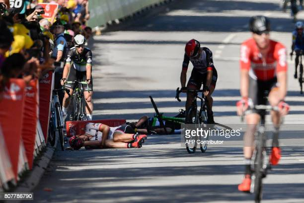 TOPSHOT Germany's John Degenkolb and Great Britain's Mark Cavendish lie on the ground after falling near the finish line at the end of the 2075 km...