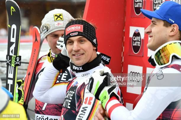 Germany's Josef Ferstl smiles next to Austria's Max Franz and Austria's Matthias Mayer after the FIS Alpine World Cup Men Super G on December 15,...