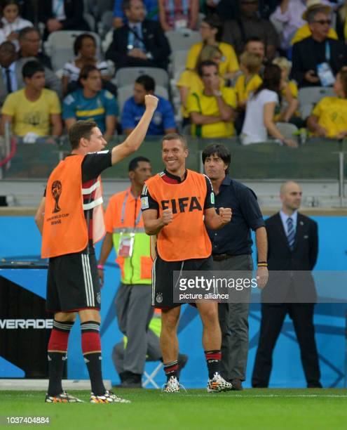 Germany's Julian Draxler, Lukas Podolski and head coach Joachim Loew react after a goal during the FIFA World Cup 2014 semi-final soccer match...