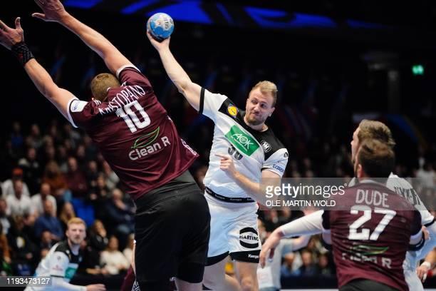 Germany's Julius Kühn vies with Latvia's Dainis Kristopans during the men's handball European Championship Preliminary Round Group C match between...