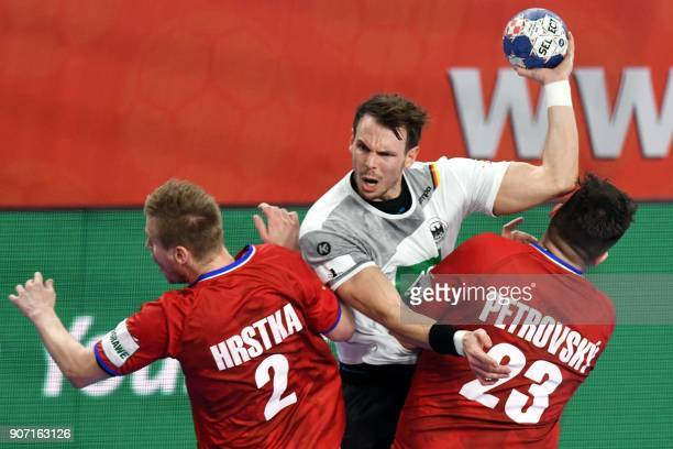 Germany's Kai Hafner vies with Czech Republic's Jakub Hrstka and Leos Petrovsky during the group II match of the Men's 2018 EHF European Handball...
