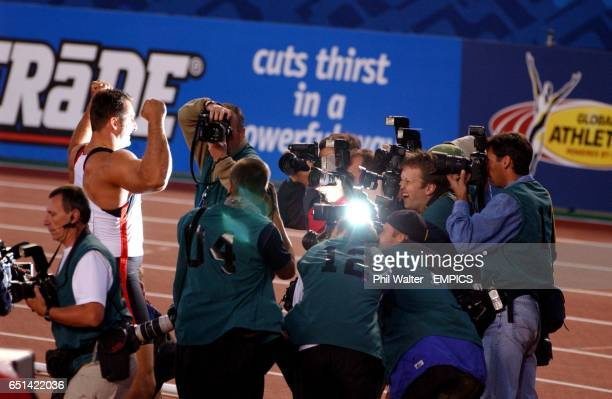 Germany's Lars Riedel hams it up for the infield photographers after winning gold in the Mens Discus