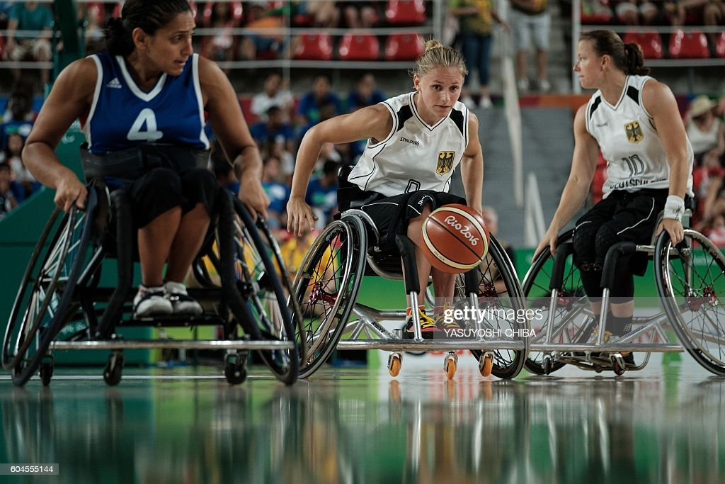 TOPSHOT - Germany's Laura Furst (C) competes against France the women's wheelchair basketball quarterfinal in the Paralympic Games at Olympic Park in Rio de Janeiro on September 13, 2016. / AFP / YASUYOSHI