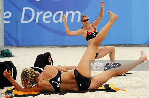 Germany's Laura Ludwig and Sara Goller strech during a training at the Olympic beach volleyballl centre in Chaoyang Park in Beijing on August...