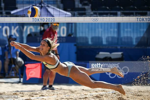 Germany's Laura Ludwig dives for the ball in their women's preliminary beach volleyball pool F match between Switzerland and Germany during the Tokyo...