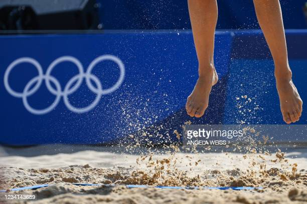 Germany's Laura Ludwig jumps for the ball in their women's preliminary beach volleyball pool F match between Switzerland and Germany during the Tokyo...