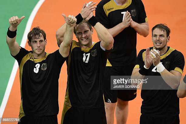 Germany's left wing Uwe Gensheimer Poland's left wing Adam Wisniewski and Germany's right back Kai Hafner celebrate their victory at the end of the...