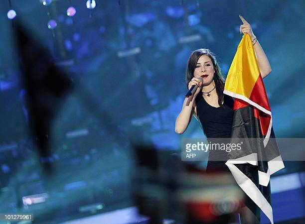 Germany's Lena MeyerLandrut sings with her national flag after winning the Eurovision Song Contest 2010 final at the Telenor Arena in Baerum near...