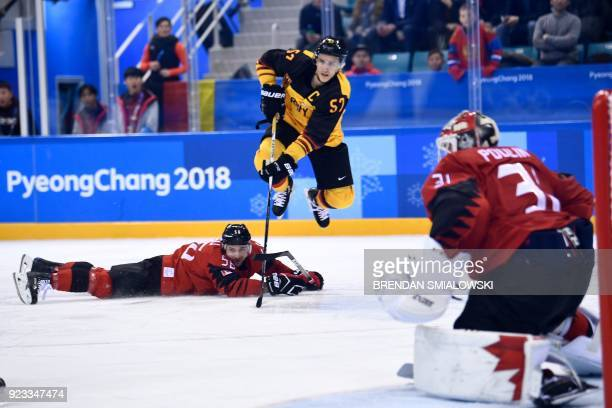 TOPSHOT Germany's Marcel Goc jumps over Canada's Maxim Noreau in the men's semifinal ice hockey match between Canada and Germany during the...