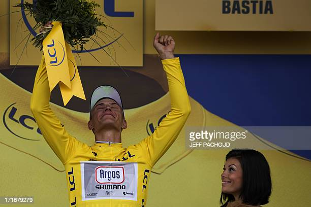 Germany's Marcel Kittel celebrates his overall leader yellow jersey on the podium after winning the 213 km first stage of the 100th edition of the...