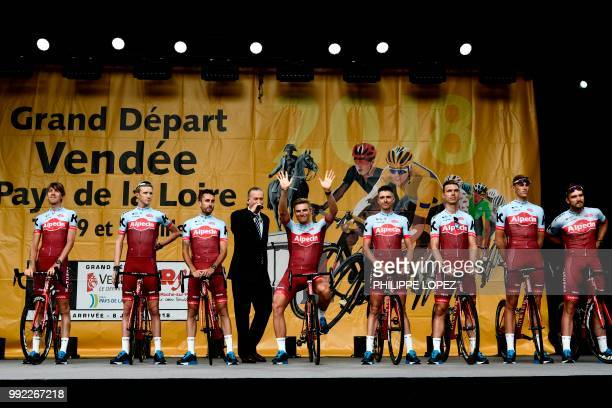 Germany's Marcel Kittel waves as riders of Switzerland's Katusha Alpecin cycling team stand on stage during the team presentation ceremony on July 5...