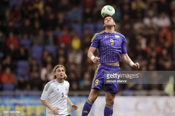Germany's Marcel Schmelzer vies for the ball with Kazakhstan's Sergey Ostapenko during the FIFA World Cup 2014 qualification group C soccer match...