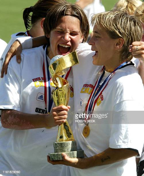 Germany's Maren Meinert and an unidentified teammate celebrate with the World Cup trophy after Germany defeated Sweden 2-1 in the final at the FIFA...