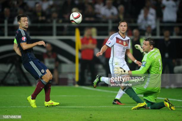 Germany's Mario Goetze and Scotland's Russell Martin and goalkeeper David Marshall vie for the ball during the UEFA EURO 2016 qualifying group D...