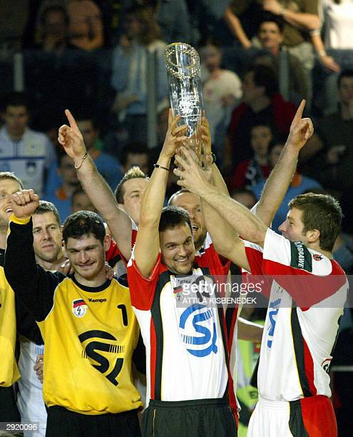 Germany's Markus Baur lifts the trophy next to goalkeeper Henning Fritz and Daniel Stephan after their victory against Slovenia in the finals of the...