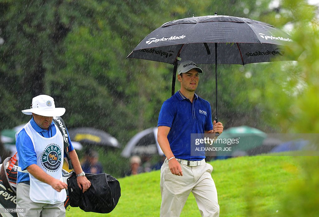 Germany's Martin Kaymer (R) walks in the rain to a shot on the 7th during the 2012 Nedbank Golf Challenge in Sun City on December 2, 2012. Kaymer won the tournament. PHOTO / Alexander Joe