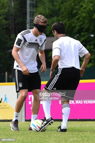 Germany's Matthias Ginter kicks the ball wearing a mask next to Germany's blind player Ali Pektas during a blind football demonstration at the...