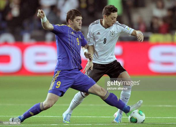 Germany's Mesut Oezil vies for the ball with Kazakhstan's Sergey Ostapenko during the FIFA World Cup 2014 qualification group C soccer match between...