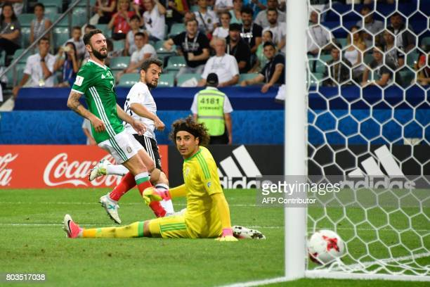 TOPSHOT Germany's midfielder Amin Younes scores in the nets of Mexico's goalkeeper Guillermo Ochoa during the 2017 Confederations Cup semifinal...