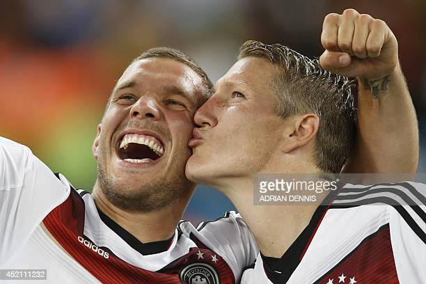 Germany's midfielder Bastian Schweinsteiger and Germany's forward Lukas Podolski take a 'selfie' after their victory in extra-time in the final...